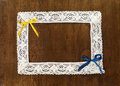 Lacy frame and colorful bows yellow blue ribbon lace with free space for your text on wooden board Stock Image