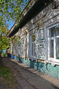 Lacy wooden house with window shutters in the shade of the leaves irkutsk streets russia Royalty Free Stock Photography