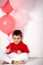 Lad with balloons portrait of happy relaxing on sofa Royalty Free Stock Photo