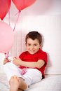 Lad with balloons portrait of happy relaxing on sofa Royalty Free Stock Photography