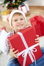 Lad with giftbox portrait of cheerful boy in santa cap holding big red and looking at camera Stock Photography