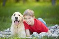 Lad and labrador portrait of cute his friendly pet lying on plaid Stock Photo