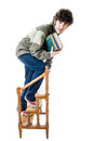 Ladder of knowledge an handsome guy maybe a student in casual clothing clambering on a small wooden library isolated on white Royalty Free Stock Image