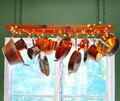 Ladder serving as a pot rack with copper pots hanging from its rungs Royalty Free Stock Photo