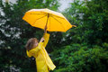 Laddie with a bright yellow umbrella in the rain he loves and rejoices behind back of boy beautiful wet bush Stock Photo