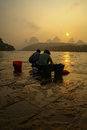 Ladies manually doing the laundry at sun rise as a new dawn break in yangshuo china Royalty Free Stock Image
