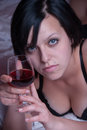 Lady at bed holding a glass of red wine Royalty Free Stock Photo