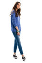 Lady in blue sweatshirt jeans and black footwear model holds cell phone style of our time Royalty Free Stock Photography