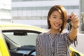 Lady with car keys a charming asian standing infront of her showing her Royalty Free Stock Images