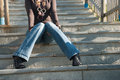 Lady in casual clothes sitting on stairs slim wearing wide legs jean pants heels shirt and big necklace hands under legs photo Royalty Free Stock Image