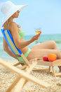 Lady with glass of champagne on beach Stock Photo