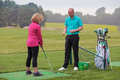 Lady golfer being taught by a golf pro to play on practise driving range Royalty Free Stock Photo