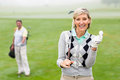 Lady golfer smiling at camera with partner behind Royalty Free Stock Photo