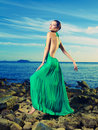 Lady in green dress on seashore beautiful a a rocky shore Stock Images