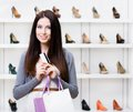 Lady hands credit card in footwear shop holds with great variety of stylish shoes Stock Image