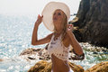 Lady in Hat and white lace dress on rocky beach Royalty Free Stock Photo