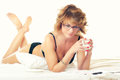 Lady in lingerie lying on bed, drinking coffee and reading magaz Royalty Free Stock Photo