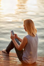 Lady looking in phone on dock Royalty Free Stock Photo
