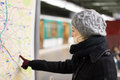 Lady looking on public transport map panel. Royalty Free Stock Photo