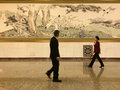 A lady and a man passing by a Chinese painting in the Great Hall of People in Beijing