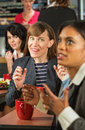 Lady mocking coworker business women at table in cafeteria Royalty Free Stock Photography