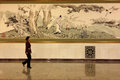 A lady passing by a Chinese painting in the Great Hall of People in Beijing