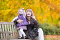 Lady playing with little toddler girl in autumn park Royalty Free Stock Photo