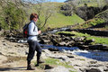 Lady rambler climbing over a stile standing by river in the yorkshire dales Stock Images
