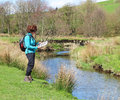 Lady rambler climbing over a stile standing by river in the yorkshire dales reading map Stock Photo