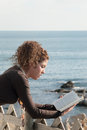 Lady reading a book at the seaside Royalty Free Stock Photo