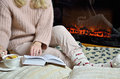 Lady reading and drinking tea by the fireplace Royalty Free Stock Photo