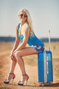 Lady ready for a trip to the seaside resort beautiful girl is dancing on sand with suitcase traveling on sea happy traveler young Stock Images