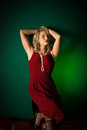 Lady in red blonde woman a dress front of a green background Royalty Free Stock Photos