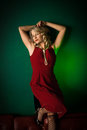 Lady in red blonde woman a dress front of a green background Stock Image