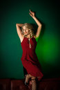 Lady in red blonde woman a dress front of a green background Stock Photo