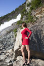 Lady in red the dress and high heels posing on a rock close to mendenhall glacier nugget waterfall juneau alaska Stock Photo