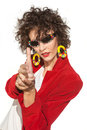Lady in red portrait of beautiful fashionable woman stylish sunglasses and coat imitating hands firing from gun Stock Images
