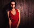 Lady in red pose on wooden background. Royalty Free Stock Photo