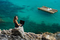 Lady is siiting on a stone on high with laptop Royalty Free Stock Photo