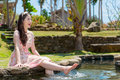Lady sitting near pond and using leg playing water Royalty Free Stock Photo