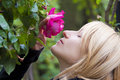 Lady  smelling a rose ih a baroque park Royalty Free Stock Image