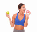 Lady in sportswear biting sugary cake wearing sports outfit against white background Stock Photography