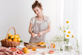 Lady standing indoors and squeezes out juice of a citruses Royalty Free Stock Photo