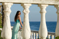 Lady standing on veranda of a beachfront home beautiful wearing long blue dress gazing the view ocean and sky as background Royalty Free Stock Images