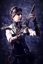 Lady steampunk portrait of a beautiful woman holding a gun over grunge background Royalty Free Stock Photography