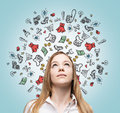 Lady is thinking about shopping. Colourful shopping icons are flying in the air. Royalty Free Stock Photo