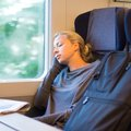 Lady traveling napping on a train blonde casual caucasian while by Stock Photo