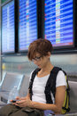 Lady waiting in airport terminal using phone Royalty Free Stock Photo