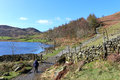 Lady walker on footpath by Watendlath Tarn at gate Royalty Free Stock Photo