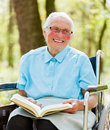 Lady in wheelchair reading bible with glasses sitting and the Royalty Free Stock Photo